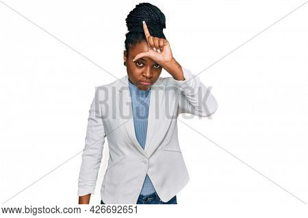 Young african american woman wearing business clothes making fun of people with fingers on forehead doing loser gesture mocking and insulting.