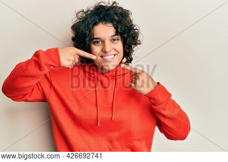 Young hispanic woman with curly hair wearing casual sweatshirt smiling cheerful showing and pointing with fingers teeth and mouth. dental health concept.