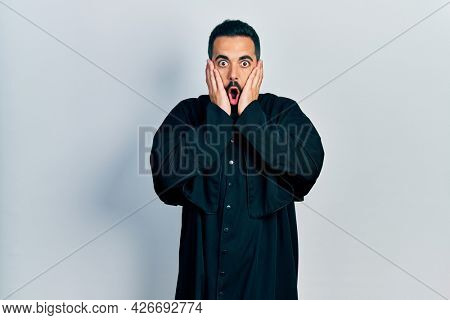Handsome hispanic man with beard wearing catholic priest robe afraid and shocked, surprise and amazed expression with hands on face
