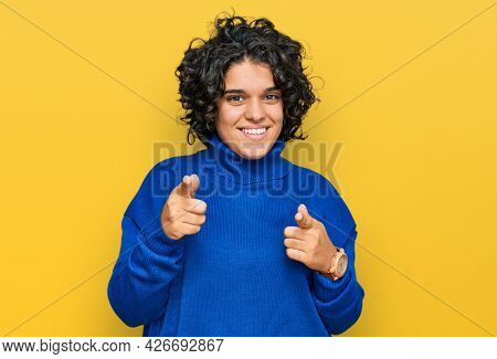 Young hispanic woman with curly hair wearing turtleneck sweater pointing fingers to camera with happy and funny face. good energy and vibes.