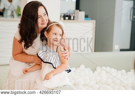 Mother And Daughter Sit By The Dry Pool With White Balls. Playroom For Children