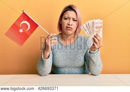 Hispanic woman with pink hair holding turkey flag and liras banknotes clueless and confused expression. doubt concept.