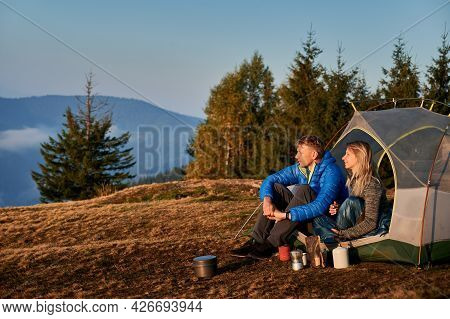 Side View Of Married Couple Of Travelers Resting In Tent On Mountain Meadow During Autumn Hike Again