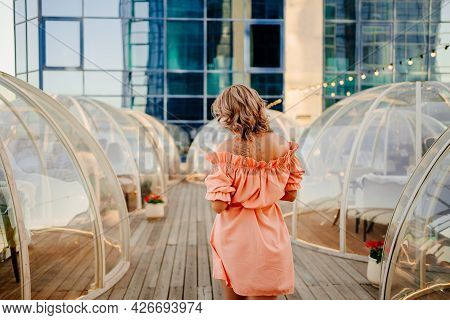 Beautiful Woman In A Pink Dress Strolls Along The Roof Between The Igloo Tables