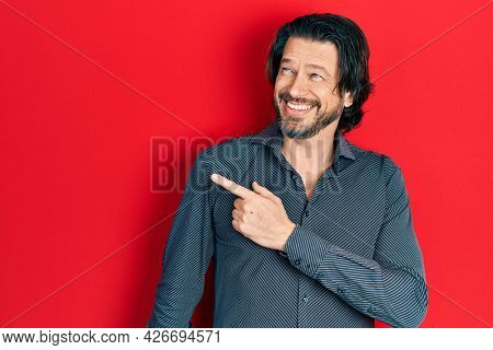 Middle age caucasian man wearing casual clothes cheerful with a smile of face pointing with hand and finger up to the side with happy and natural expression on face