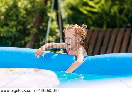 A Charming Baby Touches The Water In An Inflatable Pool In The Garden And Smiles