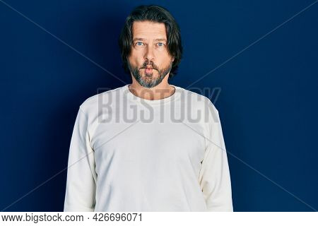 Middle age caucasian man wearing casual clothes making fish face with lips, crazy and comical gesture. funny expression.