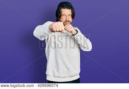Middle age caucasian man wearing casual clothes punching fist to fight, aggressive and angry attack, threat and violence