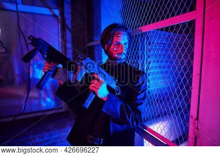 Armed special agent on a mission. Courageous man action hero with automatic guns in an industrial zone at night.