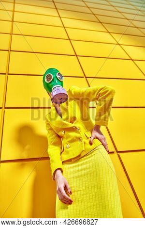 Portrait of a woman in elegant yellow suit and green gas mask posing by a yellow industrial wall. Environmental disaster, apocalypse. Fashion of the future.