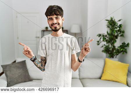 Hispanic man with beard at the living room at home smiling confident pointing with fingers to different directions. copy space for advertisement