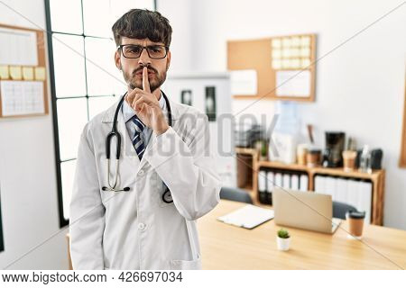 Hispanic man with beard wearing doctor uniform and stethoscope at the office asking to be quiet with finger on lips. silence and secret concept.