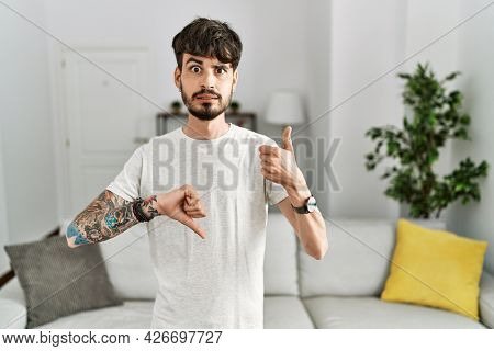 Hispanic man with beard at the living room at home doing thumbs up and down, disagreement and agreement expression. crazy conflict