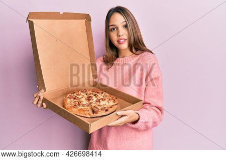Young brunette woman holding italian pizza relaxed with serious expression on face. simple and natural looking at the camera.