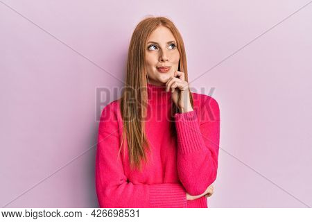 Young irish woman wearing casual clothes thinking concentrated about doubt with finger on chin and looking up wondering