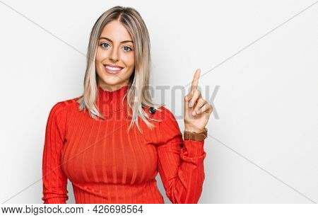 Beautiful blonde woman wearing casual clothes pointing finger up with successful idea. exited and happy. number one.
