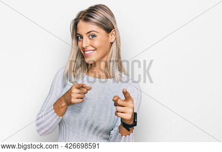 Beautiful blonde woman wearing casual clothes pointing fingers to camera with happy and funny face. good energy and vibes.