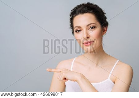 Young Beautiful Woman With Perfect Skin, Gesturing To Copy Space. Cosmetology, Beauty And Spa Concep