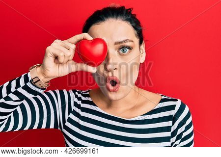 Young caucasian woman holding heart over eye scared and amazed with open mouth for surprise, disbelief face