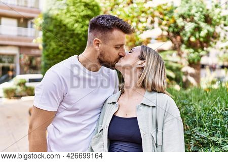 Young caucasian couple of boyfriend and girlfriend having fun outdoors on a un sunny day kissing in love