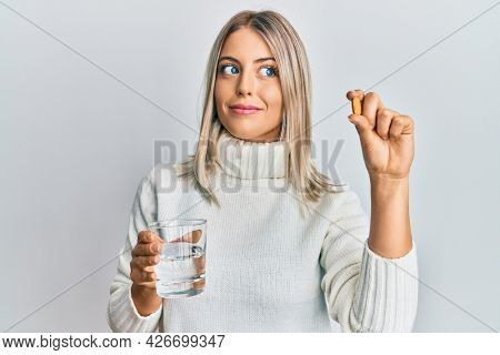 Beautiful blonde woman holding pill and glass of water smiling looking to the side and staring away thinking.
