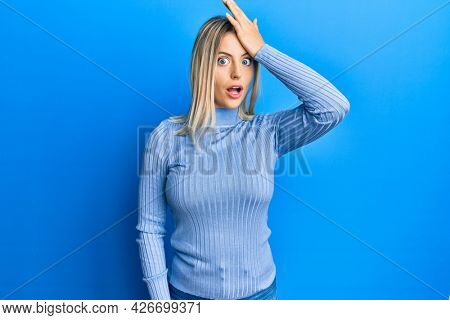 Beautiful blonde woman wearing casual clothes surprised with hand on head for mistake, remember error. forgot, bad memory concept.
