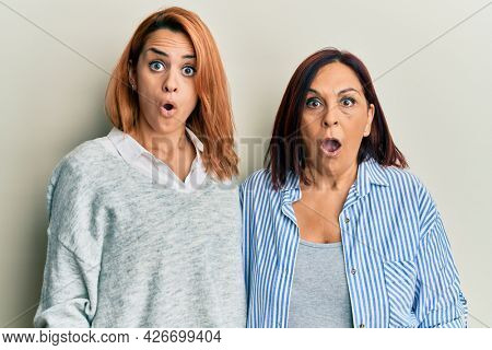 Latin mother and daughter wearing casual clothes scared and amazed with open mouth for surprise, disbelief face