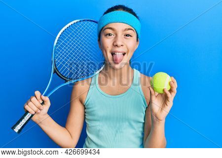 Beautiful brunette little girl playing tennis holding racket and ball sticking tongue out happy with funny expression.