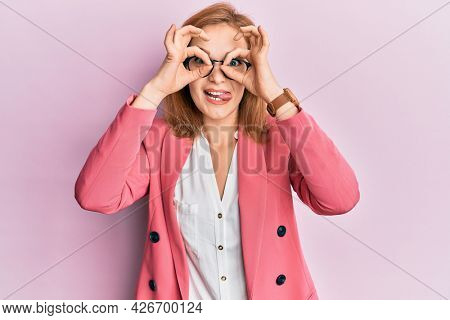 Young caucasian woman wearing business style and glasses doing ok gesture like binoculars sticking tongue out, eyes looking through fingers. crazy expression.