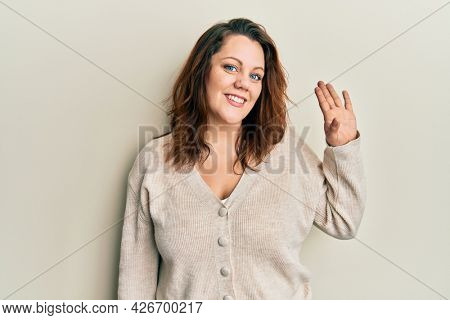 Young caucasian woman wearing casual clothes waiving saying hello happy and smiling, friendly welcome gesture