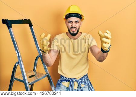 Handsome man with beard by construction stairs wearing hardhat shouting frustrated with rage, hands trying to strangle, yelling mad