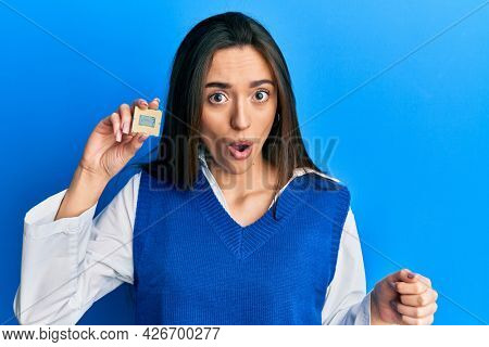 Young hispanic girl holding cpu computer processor scared and amazed with open mouth for surprise, disbelief face