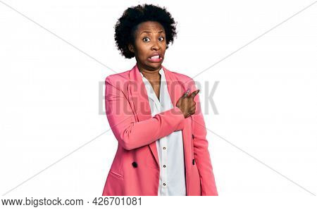 African american woman with afro hair wearing business jacket pointing aside worried and nervous with forefinger, concerned and surprised expression