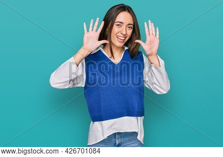 Young hispanic girl wearing casual clothes showing and pointing up with fingers number ten while smiling confident and happy.