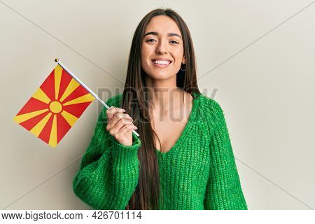 Young hispanic girl holding macedonian flag looking positive and happy standing and smiling with a confident smile showing teeth