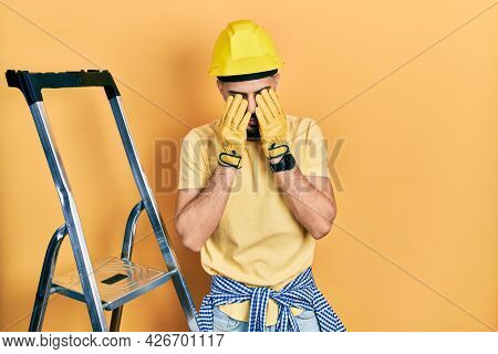 Handsome man with beard by construction stairs wearing hardhat rubbing eyes for fatigue and headache, sleepy and tired expression. vision problem
