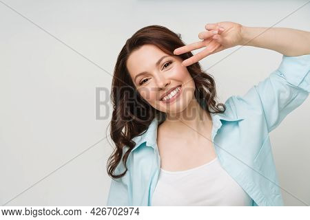 Portrait Of A Smiling Woman Showing A Victory Sign And Looking Into A Camera Isolated On A White Bac
