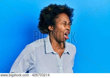 Young african american woman wearing casual clothes with hand on stomach because nausea, painful disease feeling unwell. ache concept.
