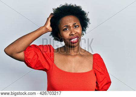 Young african american woman wearing casual clothes confuse and wonder about question. uncertain with doubt, thinking with hand on head. pensive concept.