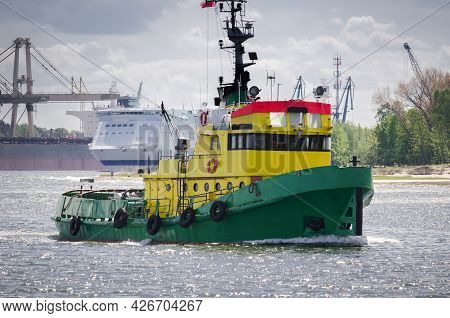 Tugboat - Auxiliary Vessel Sails In The Seaport Background