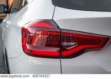 The Red Headlight Of A New Modern White Color Car. Rear Stop Light Of Prestige Suv Car. White Premiu