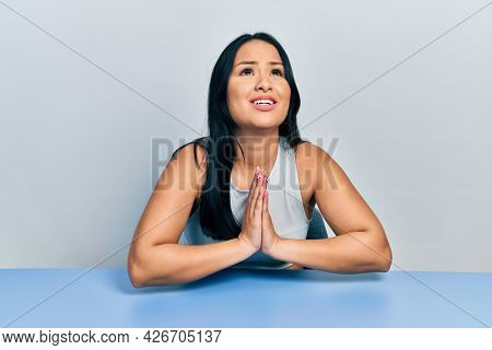 Beautiful hispanic woman with nose piercing sitting on the table begging and praying with hands together with hope expression on face very emotional and worried. begging.