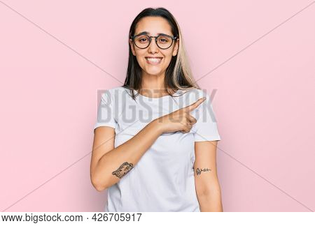 Young hispanic woman wearing casual white t shirt pointing aside worried and nervous with forefinger, concerned and surprised expression