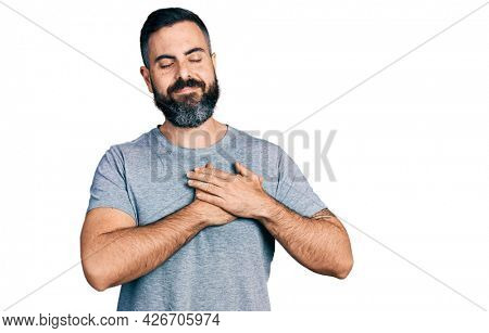 Hispanic man with beard wearing casual grey t shirt smiling with hands on chest, eyes closed with grateful gesture on face. health concept.