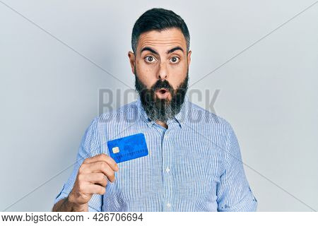Young hispanic man holding credit card scared and amazed with open mouth for surprise, disbelief face