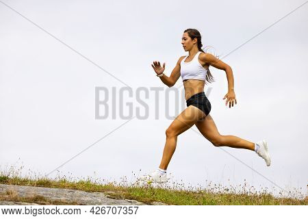 Determined Fit Female Athlete Running On Mountain Against Sky