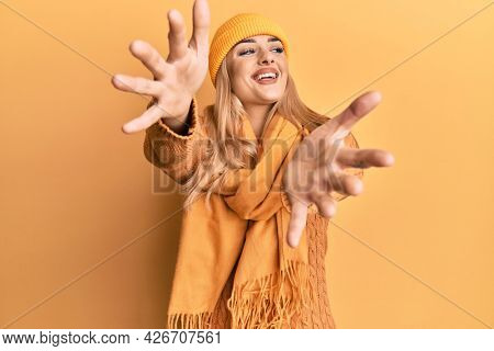 Young caucasian woman wearing wool winter sweater and cap looking at the camera smiling with open arms for hug. cheerful expression embracing happiness.