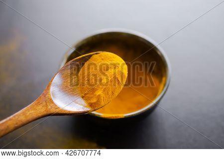 Turmeric In Wooden Spoon On Blur Turmeric In Black Cup On Black Wooden Table. Thai Organic Herb. Cur