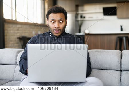 Shocked Indian Young Man Staring At Laptop Display, Feel Astonishment With A Bad News, Fired From Wo