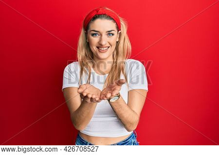 Young caucasian woman wearing casual white t shirt smiling with hands palms together receiving or giving gesture. hold and protection